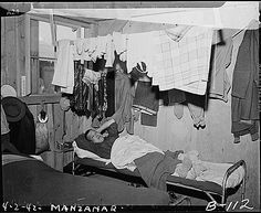 Manzanar Relocation Center, Manzanar, California. An evacuee resting on  his cot after moving his belongings into this bare barracks room. A...