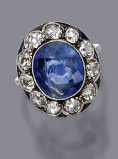 SAPPHIRE AND DIAMOND RING, CIRCA 1910 The cushion-shaped sapphire weighing approximately 8.80 carats, framed by 11 old-mine diamonds, the border decorated with calibré-cut sapphires, further enhanced with  single-cut and small rose-cut diamonds, mounted in platinum, size 7, 1 sapphire missing.