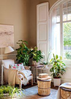 Rincón de lectura junto a la ventana con butaca con plaid y cojín de flores, taburetes-mesa de madera y mesa nido rodeada de plantas_00376792