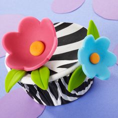 Exotic zebra stripes surround our unique cupcake topped with fondant flowers. The combination of Wilton Zebra ColorCups Standard Baking Cups and Zebra Sugar Sheets! edible decorating paper makes it easy.