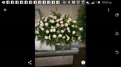 All white casket spray carnations roses lily and larkspur created by Pam Roberts