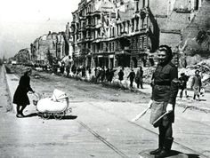 May 1945. A female Soviet soldier is controlling traffic as a German mother crosses the street.