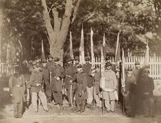 Union soldiers posing with Confederate flags that they captured in battle, each of whom was awarded a Medal of Honor for the feat, 1865. General John Gibbon, at center with his left hand on his belt, was in charge of transporting them to Washington, DC. Photograph is said to portray the 14 Medal of Honor recipients from the Battle of Fort Gregg during the Siege of Petersburg. Probably taken after Lee's surrender at Appomattox Court House.