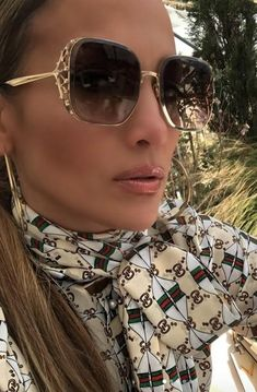 Jennifer Lopez pairs a Gucci silk shirt with web kisses print with sunglasses by Elie Saab.