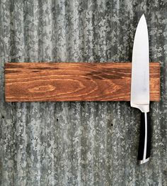 This wood knife rack keeps your knives out of the way and lookin' sharp. It's designed to sit completely flat against the wall, without any screws or magnets visible — it's embedded with a solid strip of strong rare earth magnets to hold your knives any which way you like. The wood knife rack is stained and varnished with a smooth clear gloss for protection and easy cleaning.