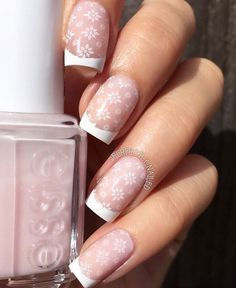 Snowflake inspired French tips. Use white and clear coat to achieve this look. After painting on the French tips you can play with small and big snowflake details and paint them on top of the nails.