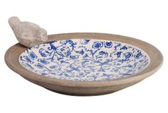 A charming floral print colors the basin of this pretty birdbath; a little ceramic bird perches on the edge.