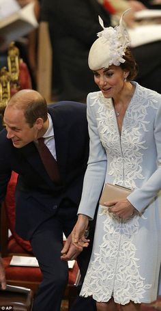 Prince William and his wife Kate share a joke with a member of the congregation, which inc...