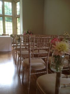 Jars of flowers attached to the chairs makes a pretty aisle www.bijouxfloral.co.uk