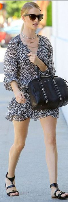 Who made  Rosie Huntington-Whiteley's cat sunglasses, gold jewelry, chain flat sandals, zebra print dress, and black leather handbag?