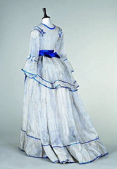 ~A blue and white striped gauze summer gown, circa 1870, the bodice with square neckline, flounced sleeves, peplum trimmed with blue satin, blue ribbon belt with later added bow~
