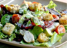 A colorful salad made with mixed baby greens, grape tomatoes, avocado, chicken breast & homemade croutons tossed with a homemade mustard vinaigrette dressing.