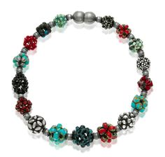 "European glass beads in bright, confident colors, tightly stitched into  3-dimensional clusters.  Strung on nylon-coated steel cable, with oxidized  sterling silver spacers.   The magnetic sterling silver clasp makes wearing a breeze.    Available in various lengths, from 16"" to 20""."