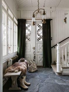 I stora entrén har paret lagt in skiffer som kommer från trädgården. Trappan leder upp till glasverandan och bostadsplanet på andra våningen.