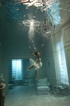 A photograph of a ballerina underwater. Interesting, creative and visually stunning. Photography as art.