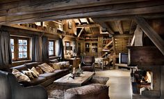 Luxury Ski Chalet Style - living room Dark leather sofas, rustic timber coffee table, fireplace