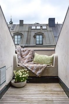 A cozy outdoor reading nook with nothing more than a bench, blanket, and pillow. Of course, the view of the city's rooftops doesn't hurt!