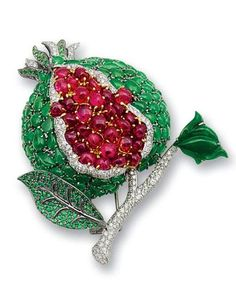 A jadeite, spinel, tsavorite garnet and diamond pomegranate brooch The seeds set with double cabochon red spinels, the skin set with jadeite cabochons of various shapes, to brilliant-cut tsavorite garnet and jadeite leaves, the branch and fruit further accented by diamonds, mounted in 18k white gold, spinels approximately 31.70 carats total, tsavorite garnets approximately 1.20 carats total, diamonds approximately 2.10 carats total, dimensions 7.3 x 6.4cm.