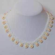 Short necklace with white and cream seed beads and offwhite pearls.