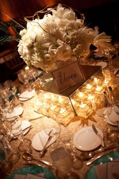 The placement of lots of votive candles placed around the mirror box, holding the flower arrangement.