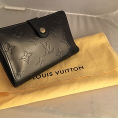 Louis Vuitton AUTHENTIC French Charcoal Wallet EUC Louis Vuitton AUTHENTIC French styled wallet.  Charcoal grey.  Has been used and is stretched and broken in.  Corners look very good.  See the pics for the wear on the inside panel and in the change purse section.  I think this is VERNIS but it might be MAT, have had for a few years. No tears.  Smoke free home.  Retails for $935.  Comes with dust bag (in excellent condition).  No tags or box. Louis Vuitton Bags Wallets