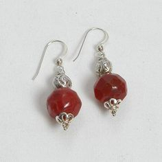 "Handmade gemstone carnelian earrings feature semi-precious, faceted carnelian gemstones, fishhook-style earwires, and sterling silver accent beads. 1 3/4"" in length. Add a necklace, pendant and bracel"