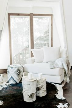 Reading nook with white chair, beautiful stool, stumps as tables and cowhide rug