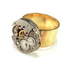 Eye-catching steampunk ring with vintage oval mechanical watch movement with exposed real ruby jewel bearings and gears set on 24 karat gold plated band. Our clockwork designs are made with authentic