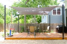 OES | Cedar deck with shade sail with steel posts and steel rails, and pea gravel