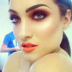 Glossy orange lipgloss on chocolate brown smokey eyes with light contouring on her cheek bones