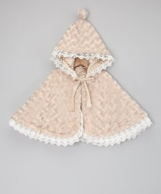 This sweetly sophisticated cape's charm lies in its thoughtful details. A modern muted minky swirl provides a neutral hue and cozy warmth, while a velvet ribbon keeps the pom-topped hood snug. Flip this stylish piece to reveal playfully polka satiny fabric trimmed with delicate vintage-inspired lace.