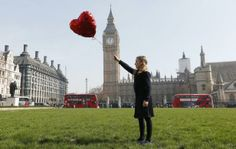 Mili Baxter poses with a red balloon while recreating the image from artist Banksy's 'There Is Always Hope' graffiti, on Parliament Square in London