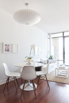 Pretty all white living and dining space with tulip table and bubble light // airy and mid century modern inspired // House Tour: Signy's Well-Curated Condo | Apartment Therapy