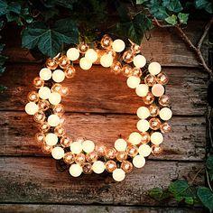 Illuminate your garden with a globe-light wreath. Our easy DIY explains how.