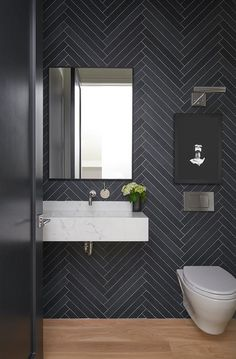 Chic contemporary powder room features a wall covered in black herringbone pattern tiles fitted behind a black framed mirror hung over a marble floating sink finished with a polished nickel wall mount faucet kit. Contemporary Bathroom Lighting, Modern Bathroom, Small Bathroom, Contemporary Toilets, Bathroom Art, Powder Room Decor, Powder Room Design, Powder Room Mirrors, Powder Room Lighting