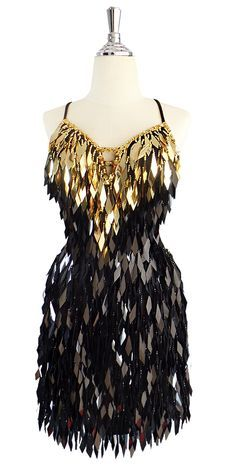 8c6feb54 A short handmade sequin dress, in diamond-shaped metallic gold and black  sequins with faceted beads, and a straight hemline.