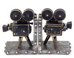 This unique set of vintage style film camera bookends would look right at home displayed in your living room, studio, home or office. Made of cold cast resin, each bookend measures 7 inches high, 5 1/4 inches long and 4 1/4 inches wide. The cameras are highly detailed and are hand-painted. They have padded foam feet on the bottoms to keep your furniture scratch free This set of 2 bookends makes the perfect gift for video enthusiasts.