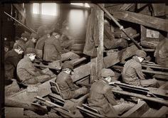 """A view of the Pennsylvania Breaker. """"Breaker Boys"""" remove rocks and other debris from the coal by hand as it passes beneath them. The dust is so dense at times as to obscure the view and penetrates the utmost recesses of the boys' lungs. South Pittston, Pennsylvania. January 1911. View full size. Photograph by Lewis Wickes Hine."""