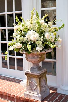 Ceremony Decor: White flowers at beginning of aisle and at the altar.