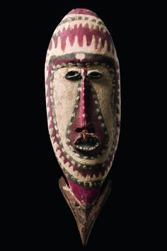 Papua New Guinea - Maprik wood, drop-shaped, painted with a thick layer of red and white pigment, contours in black, accentuated by white dots, arrow-shaped projection at the chin, pierced septum with plant fibre decor, slightly dam. (upper rim), fine fissures, base