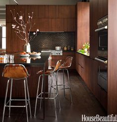 Rich woods in clean shapes, dark hues, and burnished surfaces play up the warm side of modern style in this New York City kitchen designed by Elena Frampton of Curated.   - Redbook.com