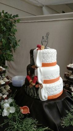 Camo wedding cake with his and hers side and shot gun shells