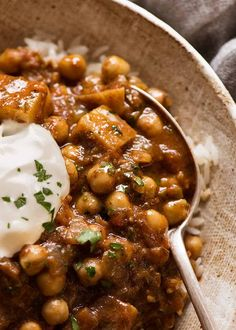 Close up of Chickpea Curry (Chana Aloo) in a bowl over coconut rice with a dollop of yogurt