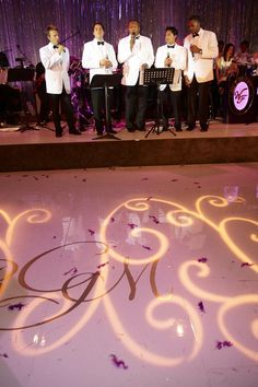 A quintet of singers dressed in white tuxedo jackets and black bow ties entertained guests with live music. The dance floor was emblazoned with the couple's initials in gold and illuminated with a scrollwork lighting projection. #weddingentertainment Photography: Dalal Photography. Read More: http://www.insideweddings.com/weddings/glam-modern-wedding-with-purple-decor-in-los-angeles-california/342/