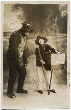 Small boy organ-grinder with a um... really large monkey (or rather, a person in a creepy monkey suit)