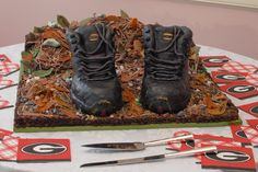 """The Groom's hiking boots. Groom's cake molded from a stack of 6 recipes of brownies for each boot.  """"Dirt""""  made from peanut butter clay, brownie crumbs and molded chocolate leaves.Rocks were peanut butter clay hand painted and pine straw was white chocolate' colored and whisked back and forth through a fine tip decorator bag onto waxed paper, then broken apart and scattered. The """"mountain"""" behind was a red velvet cake covered with cooked fudge icing."""