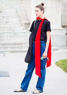 A simple black t-shirt and baggy jeans look is paired with a red single tie long scarf and black sandals.