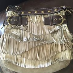Limited Edition Coach suede & leather fringed Hobo Very gently used COACH suede Gold,Silver, Tan & Beige fringe limited edition hobo bag with dark brown leather bronze studded strap & hardware. Inside has a zipper pocket & 2 pouches. The top snaps closed. Side straps are adjustable & FRINGE is IN Girls! I used to work for Coach so I have tons of it so keep Checking my Closet for more COACH goodies!! :) Coach Bags Shoulder Bags