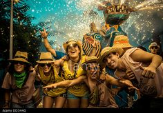 """Sitges, Spain. August 23rd, 2013: A group of friends gather under the """"Drac (dragon) de Sitges"""" for a photo as sets off his fireworks at the """"Festa Major de Sitges"""". © matthi/Alamy Live News"""