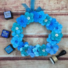 """A 8"""" grapevine wreath decorated with paper flowers. The flowers are in tones of blues and teals and the petals have two tone inked distressing giving the petals texture. In the center of the flowers is a silver and blue holographic flower sequin with a bead center that holders the taped floral wire. The wreath is hung on a teal taffeta ribbon. Since these wreaths are paper it is recommended for indoor use only! They make a precious gift or use to decorate your home!"""